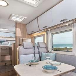 Wohnmobil Die Villa - großzügiger Essbereich mit Sitzbank in L-Form und drehbarem Fahrersitz und Beifahrersitz