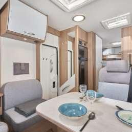 Wohnmobil Die Villa - großzügiger Essbereich mit flexiblem Tisch und zusätzlichem Sitzplatz hinter dem Beifahrersitz
