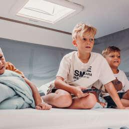 Wohnmobil Die Villa - im großen Hubbett ist ordentlich Platz und durch die Vorhänge entsteht in Windeseile eine kuschelige Höhle für Jung und Alt
